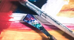 Paint brushes on a colourful background.