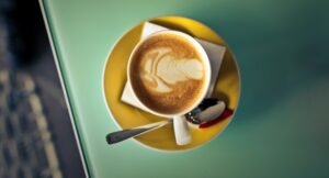 Latte with decorative foam art in a yellow cup on a green table.