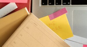 Sticky notes and notepads next to a laptop.