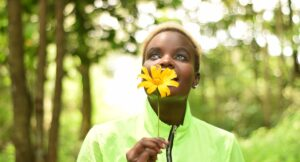 Woman in green, smelling and holding a yellow flower and looking up.