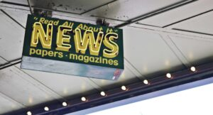 News sign stating read all about it, papers and magazines.