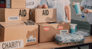 Boxes with the words Aid, Food and Medicine being given out by volunteers to help support refugees.