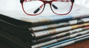 A pile of newspapers with reading glasses on the top.